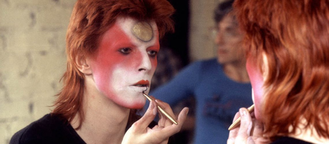 David Bowie, May 1973, makeup, London, backstage with Mick Ronson reflected behind him.